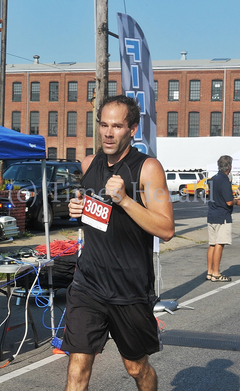 Description of . Michael Popp is the first to cross the finish line for the 9/11 Heroes Run in Norristown.  Sunday, September 8, 2013.  Photo by Adrianna Hoff/Times Herald Staff.