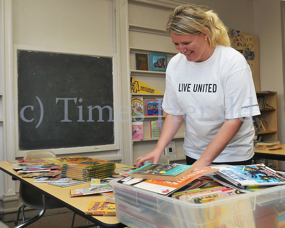 Description of . Anna Plotka organizes picture and chapter books into piles for elementary school age, middle school age, and high school age students.  Monday, September 30, 2013.  Photo by Adrianna Hoff/Times Herald Staff.