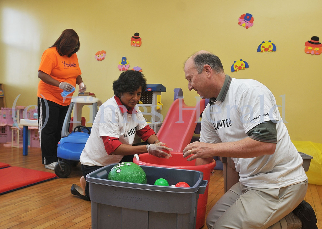 Description of . While Shyla Jagannatha and Rob Labadie clean off plastic balls, Denise Ashe works on cleaning different toys behind them.  Monday, September 30, 2013.  Photo by Adrianna Hoff/Times Herald Staff.