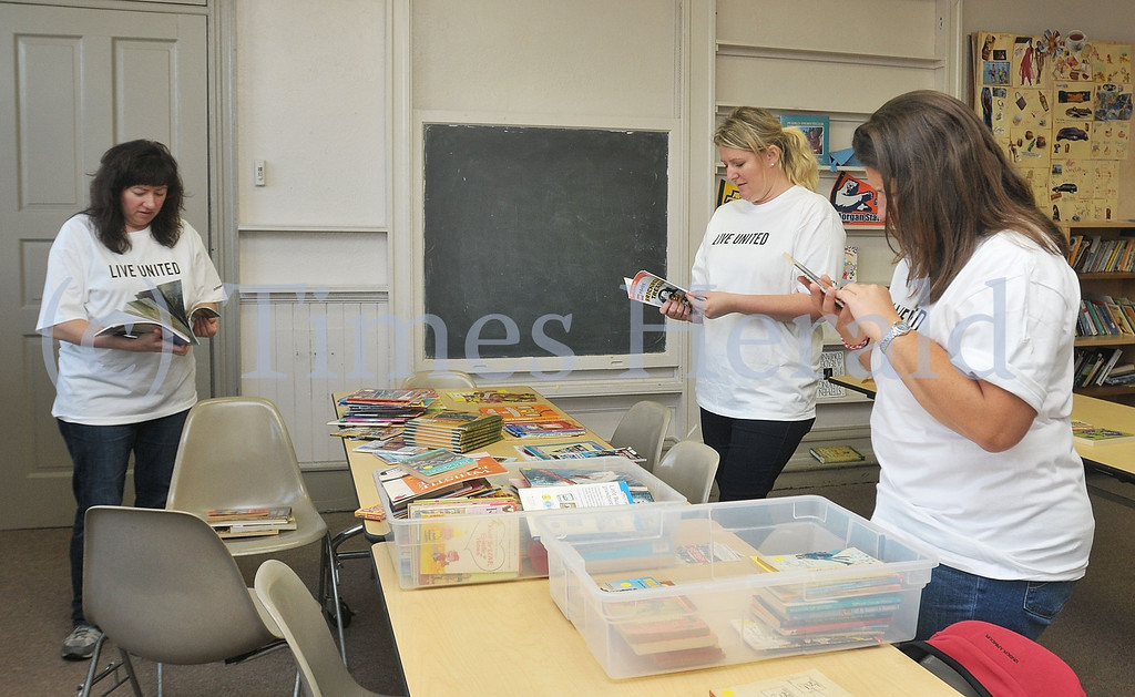 Description of . Lynne Smith, Anna Plotka, and Michele Wibel work on organizing donated books into piles based on the age of the reader.  Monday, September 30, 2013.  Photo by Adrianna Hoff/Times Herald Staff.