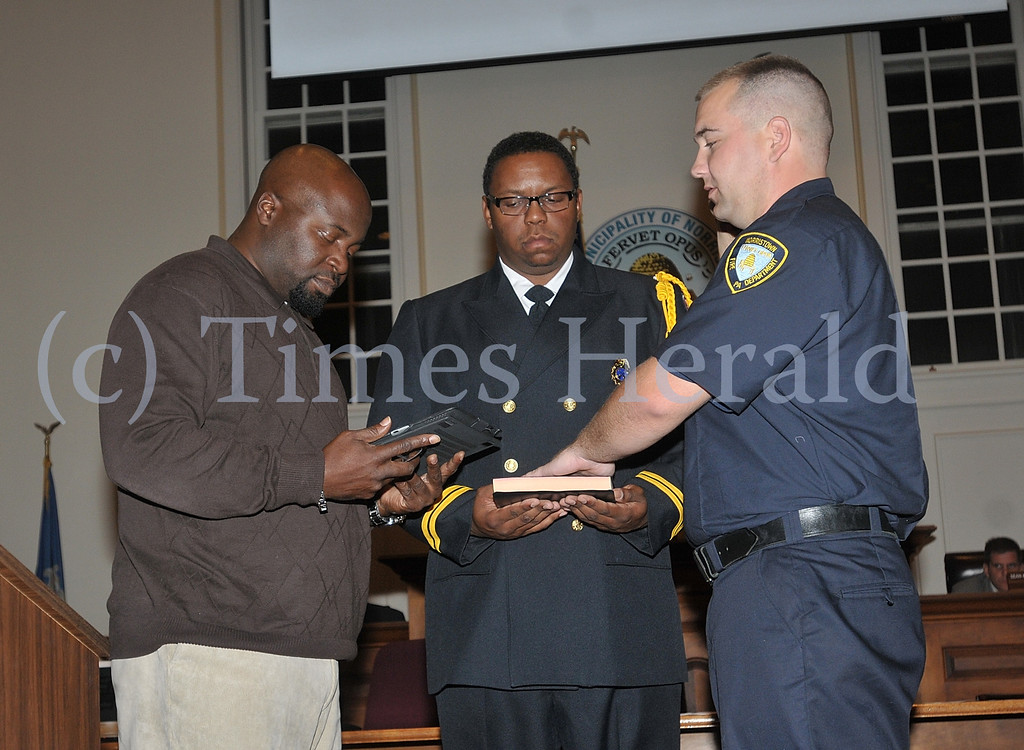 Description of . Norristown Council President Gary Simpson swears in Firefighter Andrew McIntyre to the Norristown Fire Department.  Battalion Chief Brandon Lee holds the bible that McIntyre in sworn in on.  Tuesday, October 15, 2013.  Photo by Adrianna Hoff/Times Herald Staff.