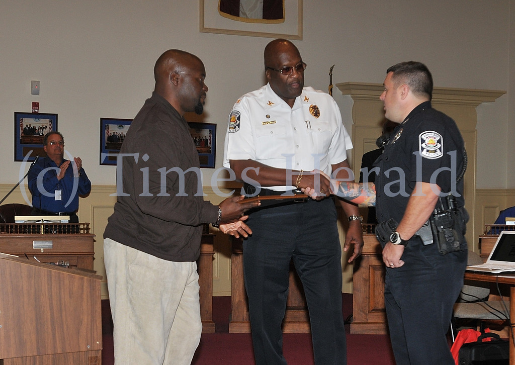 Description of . Officer Jason Hoover is awarded a certificate of commendation by Norristown Council President Gary Simpson and Police Chief Willie G. Richet at the Norristown Council Meeting on Tuesday evening.  Tuesday, October 15, 2013.  Photo by Adrianna Hoff/Times Herald Staff.