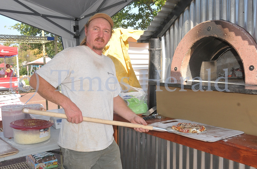 Description of . Sean Wylde from Wylde Fire Trading Company of Boyertown pulls out a fresh wood fired pizza from his oven at the Lower Providence Fall Fest.  Saturday, October 5, 2013.  Photo by Adrianna Hoff/Times Herald Staff.