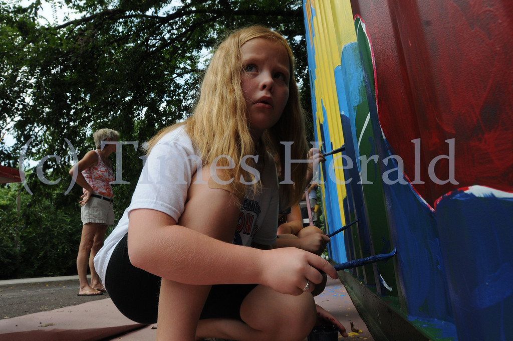 Description of . Members of the ACPPA Community Art Center paint shipping container at the Norristown Riverfront Park in Norristown Monday August 26, 2013. Times Herald Photo / Gene Walsh / times Herald Staff