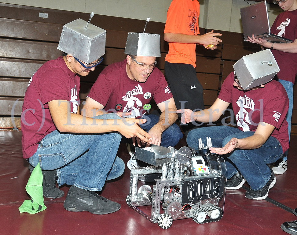 Description of . Ariosto Gomez, Brian Hildebrandt, and Nick Russell from team Foobar of Oxford, PA, look over their robot before the competition at Montgomery County Community College Physical Education Building.  Saturday, December 7, 2013.