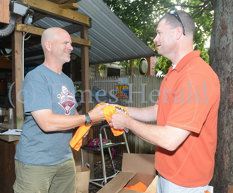 Description of . Andy Holder hands Joe Rowan his Volunteer T-shirts during the Lower Perkiomen Little League Volunteer Event at Justin's Carriage House.  Wednesday, July 16, 2014. Photo by Adrianna Hoff/Times Herald Staff.