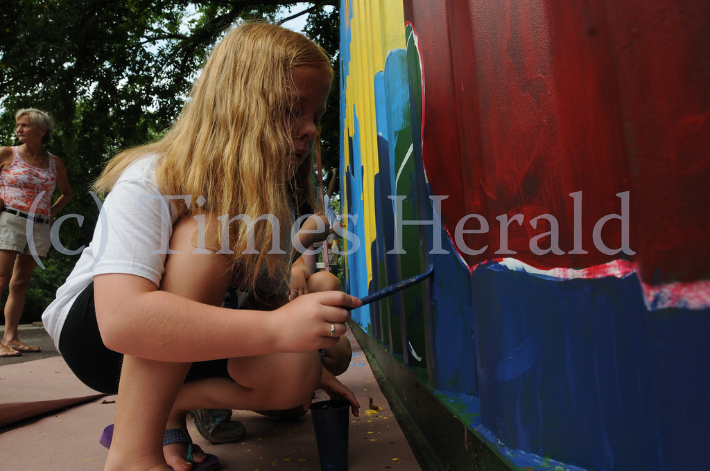 . Members of the ACPPA Community Art Center paint shipping container at the Norristown Riverfront Park in Norristown Monday August 26, 2013. Times Herald Photo / Gene Walsh / times Herald Staff